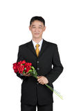 Ασιατικός επιχειρηματίας που στέκεται με το κράτημα μιας ανθοδέσμης του ροδαλού λουλουδιού Στοκ Εικόνες