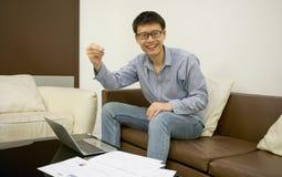Ασιατικός επιχειρηματίας που χρησιμοποιεί ένα lap-top στο καθιστικό τη νύχτα Στοκ Φωτογραφίες