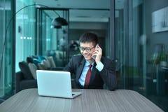 Ασιατικός επιχειρηματίας που χρησιμοποιεί το smartphone σε μια αίθουσα συνδιαλέξεων Στοκ Εικόνες