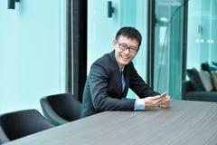 Ασιατικός επιχειρηματίας που χρησιμοποιεί το smartphone σε μια αίθουσα συνδιαλέξεων Στοκ Εικόνα
