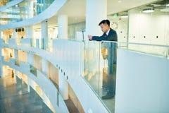 Ασιατικός επιχειρηματίας στο μπαλκόνι γυαλιού στοκ φωτογραφία με δικαίωμα ελεύθερης χρήσης