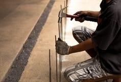 Ασιατικός εργαζόμενος με μια ράβδο σφυριών και χάλυβα Στοκ Εικόνα