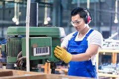 Ασιατικός εργαζόμενος στο εργοστάσιο στη μηχανή διατρήσεων Στοκ Εικόνες