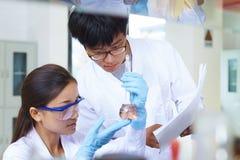 Ασιατικός εργαστηριακός δύο επιστήμονας που εργάζεται στο εργαστήριο με τους σωλήνες δοκιμής στοκ φωτογραφίες με δικαίωμα ελεύθερης χρήσης