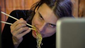 Ασιατικός ευτυχής να φάει τα νουντλς με τα κινεζικά ραβδιά φιλμ μικρού μήκους