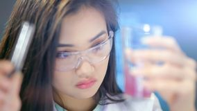 Ασιατικός θηλυκός βιολόγος που πραγματοποιεί τα χημικά πειράματα στην εργαστηριακή κινηματογράφηση σε πρώτο πλάνο απόθεμα βίντεο
