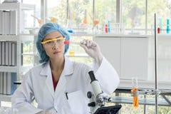 Ασιατικός θηλυκός επιστήμονας κατά τη διάρκεια των χημικών ουσιών μελέτης στοκ εικόνες