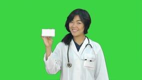 Ασιατικός θηλυκός γιατρός που παρουσιάζει ένα μπουκάλι των ταμπλετών που εξετάζουν τη κάμερα σε μια πράσινη οθόνη, κλειδί χρώματο απόθεμα βίντεο