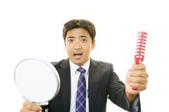 Ασιατικός καθρέφτης χεριών εκμετάλλευσης ατόμων με τη βούρτσα γηα τα μαλλιά Στοκ φωτογραφία με δικαίωμα ελεύθερης χρήσης
