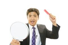Ασιατικός καθρέφτης χεριών εκμετάλλευσης ατόμων με τη βούρτσα γηα τα μαλλιά Στοκ Εικόνες