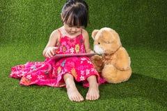 Ασιατικός κινεζικός υπολογιστής ταμπλετών παιχνιδιού μικρών κοριτσιών με το teddy bea Στοκ Εικόνες