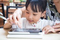 Ασιατικός κινεζικός υπολογιστής ταμπλετών παιχνιδιού μικρών κοριτσιών με το mothe της Στοκ Εικόνες