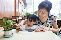Ασιατικός κινεζικός υπολογιστής ταμπλετών παιχνιδιού μικρών κοριτσιών με το mothe της Στοκ Φωτογραφία