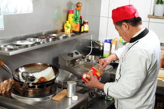Ασιατικός μάγειρας που βάζει τα καρυκεύματα μαγειρεύοντας στοκ φωτογραφία με δικαίωμα ελεύθερης χρήσης