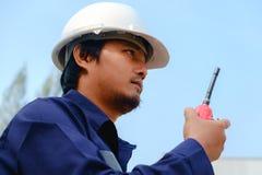 Ασιατικός μηχανικός στο μπλε κράνος ασφάλειας ασφάλειας ομοιόμορφο και άσπρο Στοκ Εικόνες
