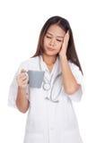 Ασιατικός νέος θηλυκός γιατρός που αρρωσταίνεται με ένα φλιτζάνι του καφέ Στοκ εικόνα με δικαίωμα ελεύθερης χρήσης