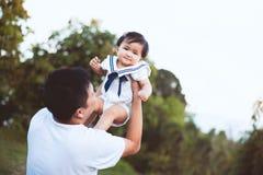Ασιατικός πατέρας που φέρνει την κόρη του επάνω στον αέρα στοκ φωτογραφία