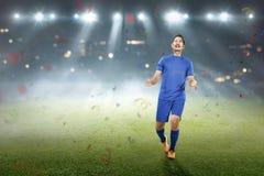 Ασιατικός ποδοσφαιριστής εορτασμού μετά από να σημειώσει έναν στόχο Στοκ Εικόνες