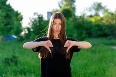 Ασιατικός σκοτεινός-μαλλιαρός καφετής-eyed κοριτσιών Το καλοκαίρι υπαίθρια Αναταραχή συγκίνησης Δείχνει τα δάχτυλά του κάτω και μ στοκ εικόνες με δικαίωμα ελεύθερης χρήσης