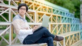 Ασιατικός σπουδαστής ατόμων που χρησιμοποιεί το lap-top στην ευθυμία στάσεων στοκ φωτογραφία με δικαίωμα ελεύθερης χρήσης