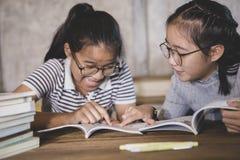 Ασιατικός σπουδαστής δύο που διαβάζει ένα σχολικό βιβλίο με τη συγκίνηση ευτυχίας στοκ εικόνα