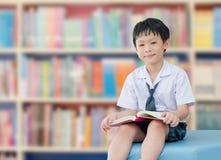 Ασιατικός σπουδαστής αγοριών στη σχολική βιβλιοθήκη Στοκ Εικόνες
