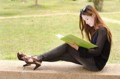 Ασιατικός σπουδαστής γυναικών που φαίνεται σχεδιάγραμμα στοκ εικόνες