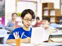 Ασιατικός σπουδαστής δημοτικών σχολείων που μελετά στην κατηγορία στοκ εικόνες