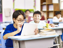 Ασιατικός σπουδαστής δημοτικών σχολείων που χρησιμοποιεί την ταμπλέτα στην τάξη στοκ εικόνες με δικαίωμα ελεύθερης χρήσης