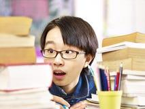 Ασιατικός στοιχειώδης μαθητής που συγκλονίζεται από το φόρτο εργασίας στοκ εικόνες