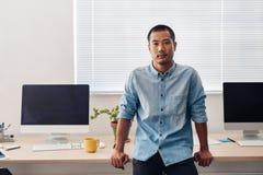 Ασιατικός σχεδιαστής που κλίνει σε ένα γραφείο σε ένα γραφείο Στοκ φωτογραφίες με δικαίωμα ελεύθερης χρήσης
