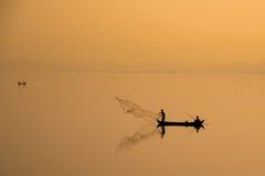 Ασιατικός τρόπος ζωής: ψαράς που ρίχνει ένα δίχτυ στη λίμνη στην ανατολή, αγροτική στην Ταϊλάνδη Στοκ φωτογραφία με δικαίωμα ελεύθερης χρήσης