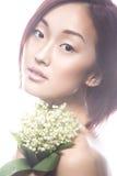 Ασιατικός τύπος κοριτσιών μόδας όμορφος με τη λεπτή φυσική σύνθεση και τα λουλούδια Πρόσωπο ομορφιάς Στοκ Φωτογραφίες