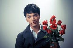 Ασιατικός τύπος με τα κόκκινα τριαντάφυλλα στο αναδρομικό ύφος Στοκ Φωτογραφία