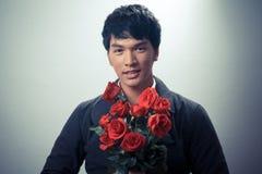 Ασιατικός τύπος με τα κόκκινα τριαντάφυλλα στο αναδρομικό ύφος Στοκ φωτογραφία με δικαίωμα ελεύθερης χρήσης