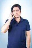 Ασιατικός τύπος με το κινητό τηλέφωνο διαθέσιμο στο μπλε υπόβαθρο Στοκ Φωτογραφίες