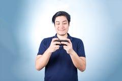 Ασιατικός τύπος με το κινητό τηλέφωνο διαθέσιμο, στο μπλε υπόβαθρο Στοκ Φωτογραφία