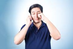 Ασιατικός τύπος με το κινητό τηλέφωνο διαθέσιμο, στο μπλε υπόβαθρο Στοκ Εικόνα