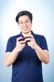 Ασιατικός τύπος με το κινητό τηλέφωνο διαθέσιμο, στο μπλε υπόβαθρο Στοκ φωτογραφίες με δικαίωμα ελεύθερης χρήσης