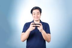 Ασιατικός τύπος με το κινητό τηλέφωνο διαθέσιμο, στο μπλε υπόβαθρο Στοκ Εικόνες