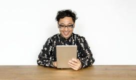 Ασιατικός τύπος με eyeglasses που χρησιμοποιούν την ψηφιακή ταμπλέτα Στοκ Φωτογραφία