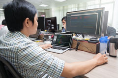 Ασιατικός υπεύθυνος για την ανάπτυξη που χρησιμοποιεί τη συνεδρίαση φορητών προσωπικών υπολογιστών Στοκ Φωτογραφία