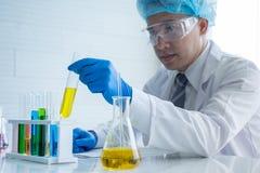 Ασιατικός φαρμακοποιός επιστημόνων που κρατά τον κίτρινο σωλήνα με μια υγρή χημική λύση Στοκ φωτογραφία με δικαίωμα ελεύθερης χρήσης