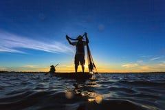 Ασιατικός ψαράς στην ξύλινη βάρκα που πετά ένα δίχτυ για τη σύλληψη Στοκ Εικόνα