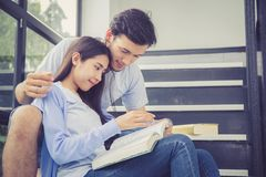 Ασιατικός όμορφος άνδρας ζεύγους και όμορφο βιβλίο και χαμόγελο ανάγνωσης γυναικών Στοκ Εικόνα