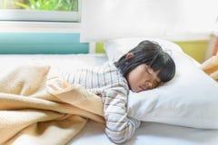 Ασιατικός ύπνος κοριτσιών στο κρεβάτι που καλύπτεται με το κάλυμμα Στοκ Φωτογραφίες