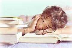 Ασιατικός ύπνος παιδιών διαβάζοντας στο κρεβάτι Κορίτσι με τα γυαλιά Στοκ Φωτογραφίες