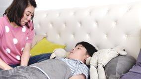 Ασιατικό άρρωστο αγόρι, που βρίσκεται στο κρεβάτι, μητέρα που ελέγχει τη θερμοκρασία του, απόθεμα βίντεο