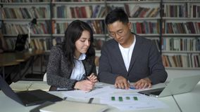 Ασιατικό άτομο ζευγών και θηλυκή εργασία γέλιου στο πρόγραμμα στη βιβλιοθήκη φιλμ μικρού μήκους