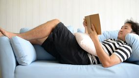 Ασιατικό άτομο που βρίσκεται στον καναπέ και που διαβάζει το βιβλίο στο σπίτι απόθεμα βίντεο